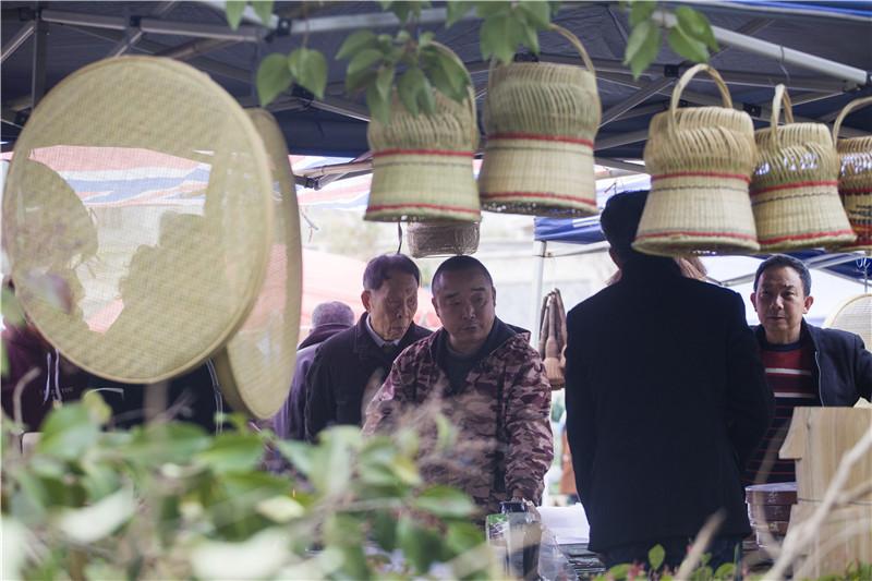 2月22日,在将乐备耕圩上手艺上刚摆上商品就有顾客前来咨询。董观生摄.jpg
